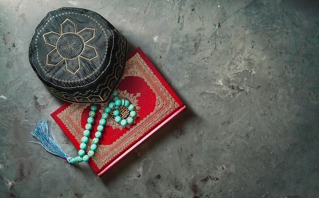 Koran und rosenkranz auf schwarz isoliert