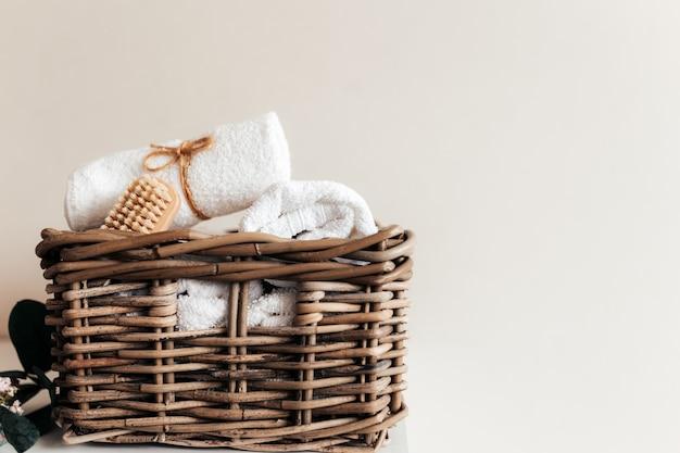 Korb mit badzubehör. ein satz gerollter und gefalteter handtücher, fußbürste. haushaltskonzept. hotelreinigungskonzept.