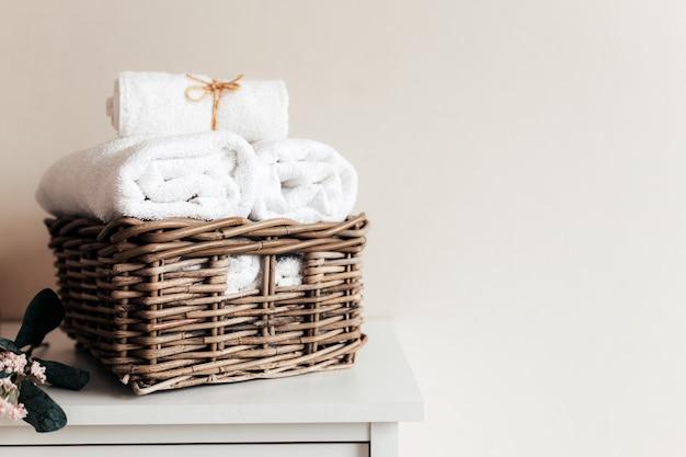 Korb mit badzubehör. ein satz gerollter und gefalteter handtücher. hotelreinigungskonzept.