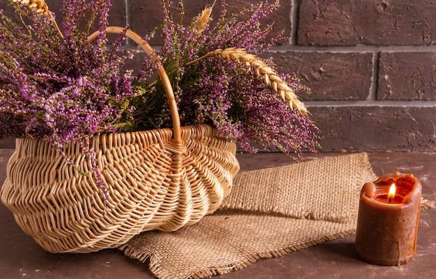 Korb mit blumen auf braunem hintergrund, lila heide und atmosphärischem kerzenkopierraum