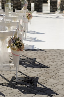 Korb mit blumen auf der rückenlehne eines stuhls bei einer hochzeitszeremonie, selektiver fokus