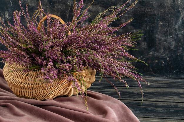 Korb mit blumen auf schwarzem hintergrund lila heidekraut