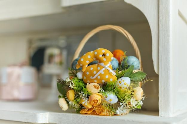 Korb mit blumen, eiern, federn und einem spielzeughasen mit bunten pastelleiern auf dem küchenschranktisch verziert. frühlings-osterkomposition.