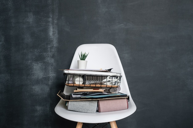 Korb mit büromaterial, gefalteten textilmustern, geschäftsdokumenten, laptop und blumentopf mit kleiner grüner pflanze auf weißem stuhl