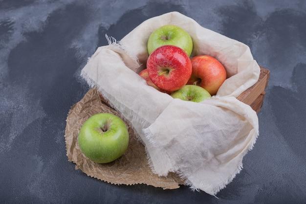 Korb mit bunten äpfeln im dunkeln.