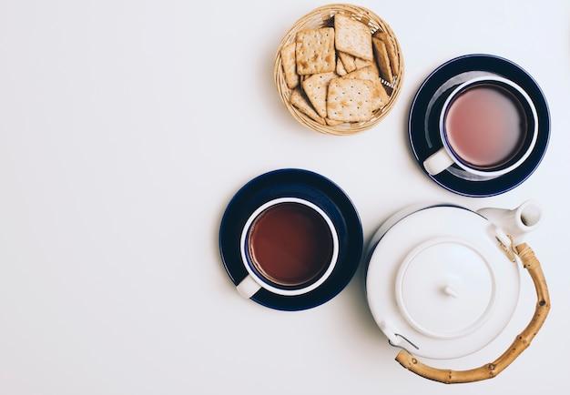 Korb mit crackern; tasse kaffee und teekanne auf weißem hintergrund
