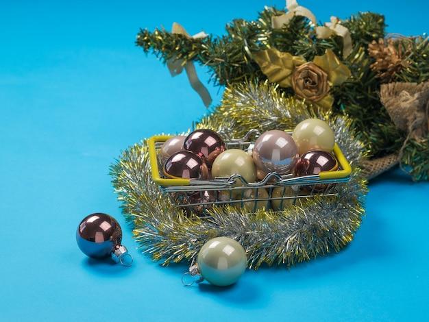 Korb mit dekorationen und weihnachtsbaum auf einer blauen oberfläche