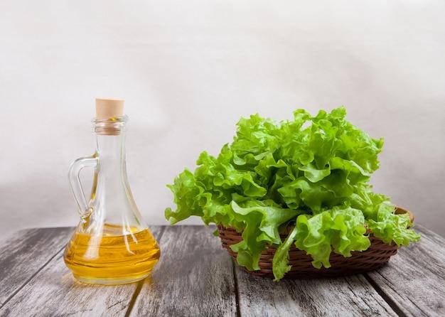 Korb mit einem grünen salat und einer butter in einem glasdekantiergefäß ist auf einem holztisch