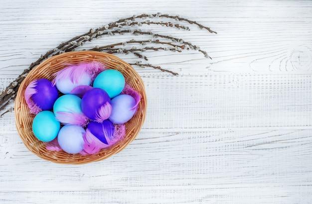 Korb mit farbigen eiern auf einem weißen hintergrund. konzept fröhliche ostern.
