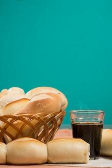 Korb mit französischem brot auf einem tisch und einem glas kaffee
