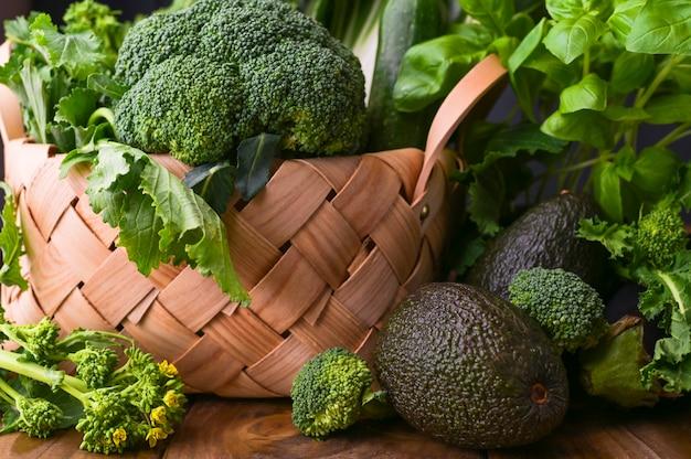 Korb mit frischem grünem gemüse auf einem hölzernen hintergrund. avocados, brokkoli, cime di rapa andere grüns. freier platz für text. speicherplatz kopieren.