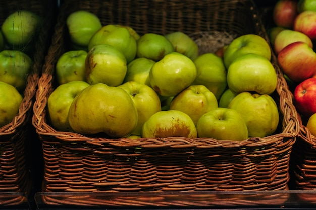 Korb mit frischen grünen äpfeln im lebensmittelgeschäft bild mit selektivem fokus hochwertiges foto