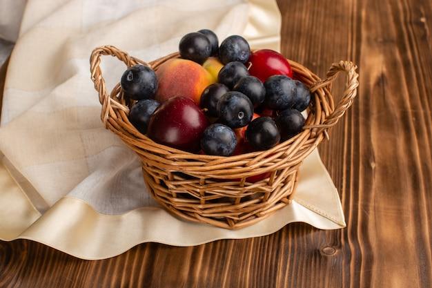 Korb mit frutis blackthorns pflaumen und pfirsichen auf holz