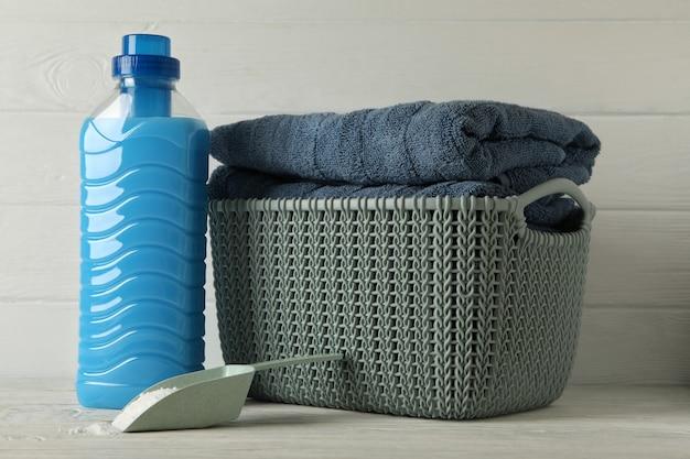 Korb mit handtüchern, schaufel mit pulver und reinigungsmittel auf holz