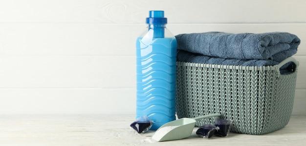 Korb mit handtüchern, wäschekapseln, schaufel mit pulver und reinigungsmittel auf holztisch