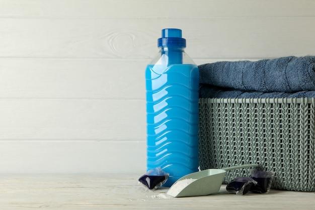 Korb mit handtüchern, wäschekapseln, schaufel mit pulver und waschmittel auf holzhintergrund
