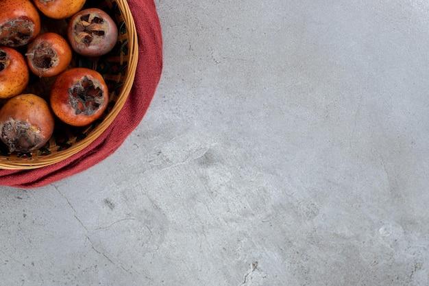 Korb mit kakis mit samen, die auf dem marmortisch entfernt wurden.