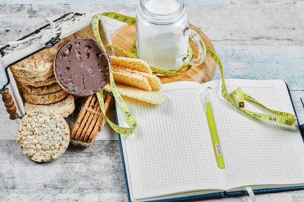 Korb mit keksen und ein glas milch auf einem holztisch mit einem notizbuch.