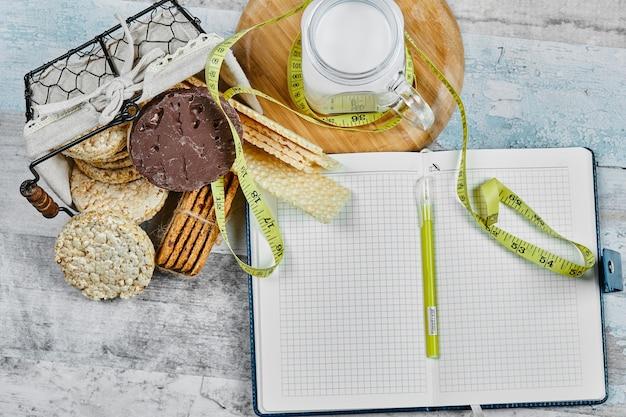 Korb mit keksen und ein glas milch auf einem marmortisch mit notizbuch und stift.