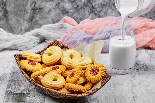 Korb mit keksen und ein glas milch mit einer tischdecke.