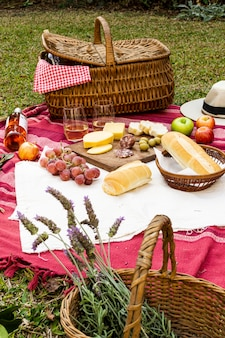 Korb mit lavendel neben picknick-leckereien