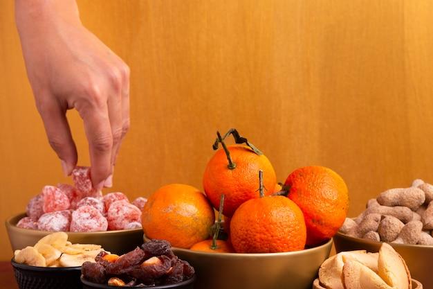 Korb mit mandarinen mit chinesischen delikatessen des neuen jahres