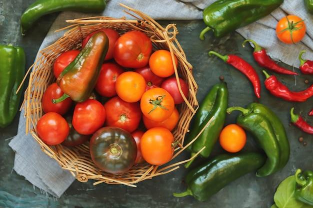 Korb mit natürlichem gemüse auf dem tisch, reifen tomaten und paprika, hausmannskost