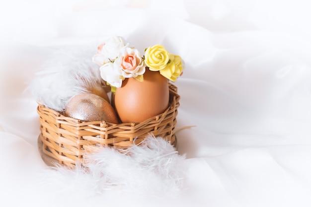 Korb mit ostern verzierten braunen eiern mit aprikosenweißen und rosa blüten. urlaub-hintergrund. osterferien im frühling.