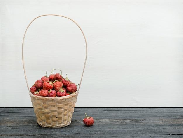 Korb mit reifen erdbeeren auf einem schwarzen tisch