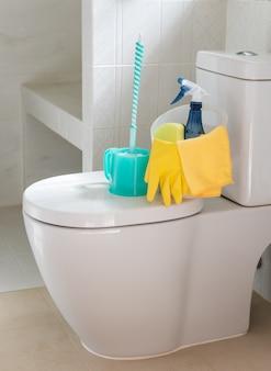 Korb mit reinigungsmitteln auf der toilettenschüssel im modernen badezimmer