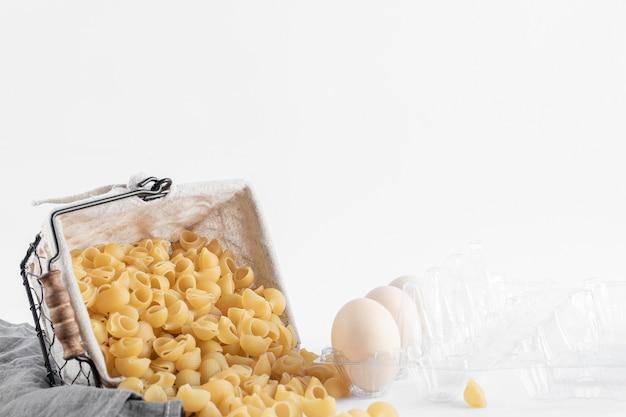 Korb mit rohen nudeln und eiern im behälter auf weißer oberfläche.