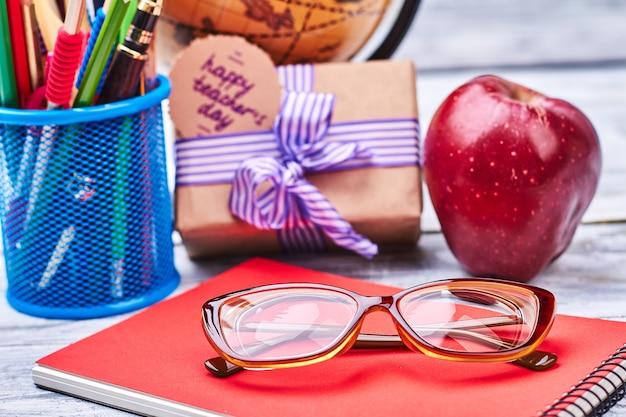 Korb mit schreibwaren und gläsern. apple, notebook und geschenkbox. aufrichtige wünsche an den lehrer.