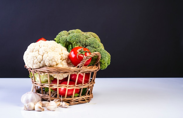 Korb mit tomaten, brokkoli und blumenkohl auf weißer und schwarzer oberfläche