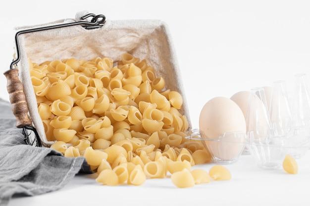 Korb mit trockenen nudeln und eiern auf weiß.