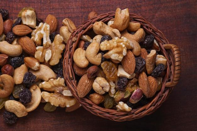 Korb mit trockenfrüchten (pistazie, rosinen, mandeln, erdnüsse, walnüsse) auf holzbrett (aus der vogelperspektive)