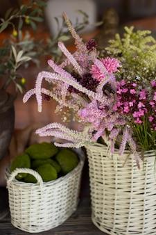 Korb mit wildblumen. sommerviolettblumen im strohkorb.