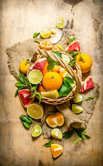 Korb mit zitrusfrüchten - grapefruit, orange, mandarine, zitrone, limette.