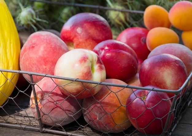 Korb von pfirsichen auf einem holztisch