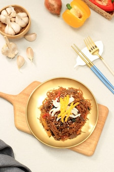 Koreanische authentische küche, japchae oder glasnudeln gebraten mit gemüse und fleisch in goldener platte.