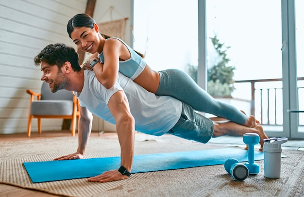 Koreanische frau des netten paares und muskulöser mann in der sportkleidung, die plankenübung im wohnzimmer zu hause macht. gesunder lebensstil, sport, yoga, fitness.
