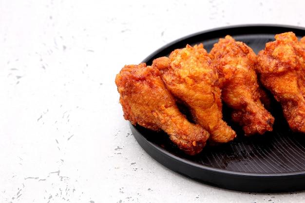 Koreanische gebratenes hühnerflügel lokalisiert auf einem grauen hintergrund im studio.