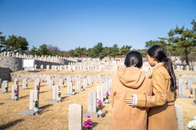 Koreanische leute vor grabstein im grab des koreakrieges