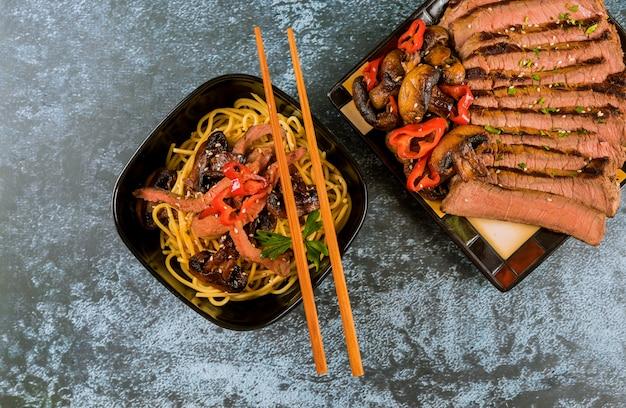 Koreanische spaghetti catelli mit gegrilltem rindfleisch und champignons.
