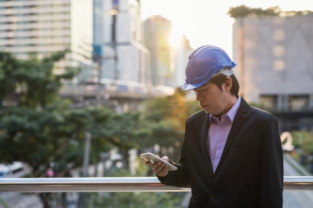 Koreanischer architekt ingenieur, 40 jahre mittleres alter, mit schutzhelm, der smartphone verwendet, um projektplan blueprinnt und zeitachse auf baustelle in der stadt bei sonnenuntergang zu überprüfen. schwerindustrie mit technologie.