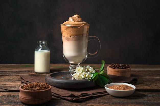 Koreanischer dalgona-kaffee mit schaum und eis an einer braunen wand. seitenansicht, horizontal. ein belebendes getränk.