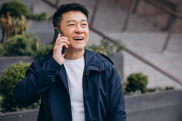 Koreanischer typ, der telefon außerhalb dieser baumkrone benutzt