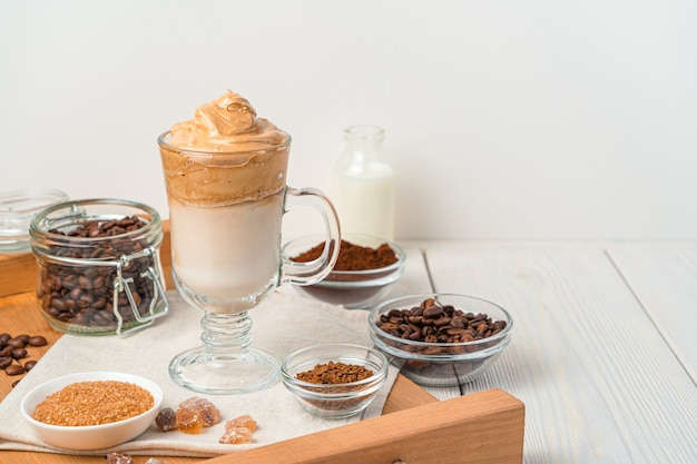 Koreanisches belebendes getränk mit geschlagenem kaffeeschaum und milch an einer weißen wand. dalgon-kaffee. seitenansicht, kopienraum.