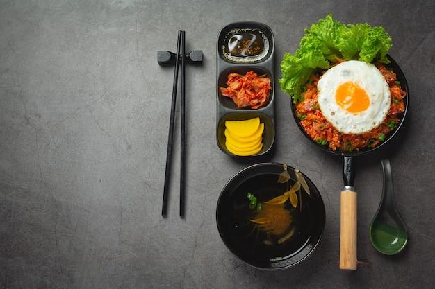 Koreanisches essen. gebratener reis mit kimchi mit spiegelei servieren