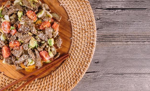 Koreanisches gericht. dünn geschnittenes rindfleisch mit gemüse. ansicht von oben.