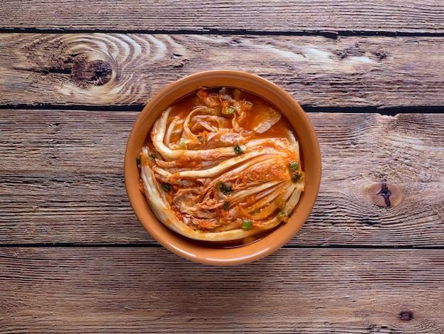 Koreanisches kimchi vom chinakohl auf einem dunklen holztisch.